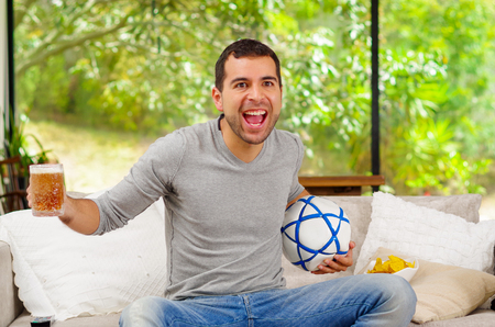enthusiastically: Hispanic man wearing denim jeans with grey sweater sitting in sofa enthusiastically cheerful facial expression watching tv holding beer and football .
