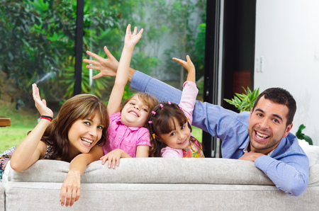 Beautiful hispanic family of four posing with heads sticking up from back of sofa looking at camera smiling. 免版税图像