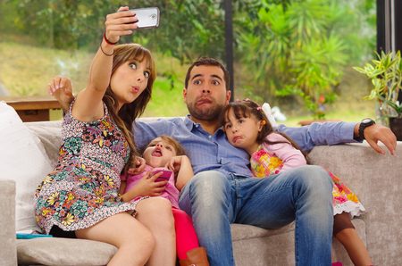 adult child: Family portrait of father, mother and two daughters sitting together in sofa posing for selfie making funny faces.