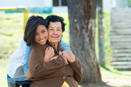 hugging: Young girl standing behind grandmother hugging and embracing in outdoors environment. Stock Photo