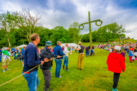 midsummer pole: GOTHENBURG, SWEDEN - JUNE 19, 2015: Unknown people raising the maypole for the traditional Midsummer celebration in Gunnebo Castle Editorial