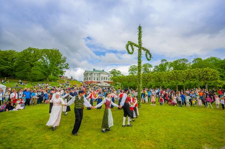 gunnebo: GOTHENBURG, SWEDEN - JUNE 19, 2015: Unknown dancers in traditional swedish dress dancing around the maypole for Midsummer celebration in Gunnebo Castle