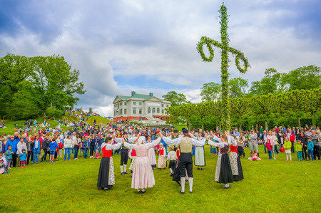 GOTHENBURG, SWEDEN - JUNE 19, 2015: Unknown dancers in traditional swedish dress dancing around the maypole for Midsummer celebration in Gunnebo Castle Zdjęcie Seryjne - 45565644