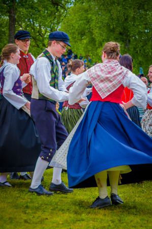 maypole: GOTHENBURG, SWEDEN - JUNE 19, 2015: Unknown dancers in traditional swedish dress dancing around the maypole for Midsummer celebration in Gunnebo Castle