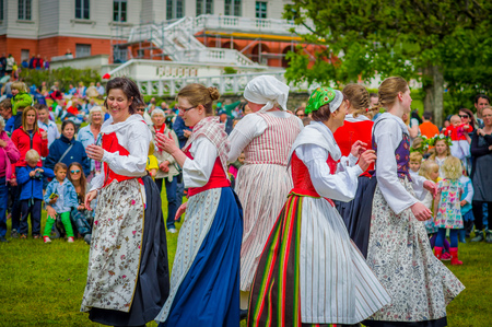 gunnebo: GOTHENBURG, SWEDEN - JUNE 19, 2015: Unknown dancers in traditional swedish dress dancing around the maypole for Midsummer celebration in Gunnebo Castle