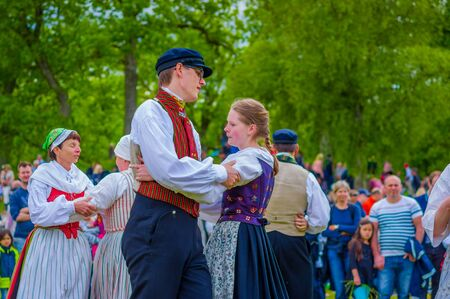 midsummer pole: GOTHENBURG, SWEDEN - JUNE 19, 2015: Unknown dancers in traditional swedish dress dancing around the maypole for Midsummer celebration in Gunnebo Castle