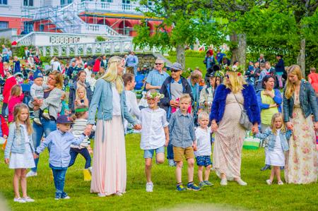 gothenburg: GOTHENBURG, SWEDEN - JUNE 19, 2015: Cheerful people dancing around the maypole during Midsummer celebration in Gunnebo Castle