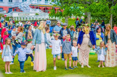 gunnebo: GOTHENBURG, SWEDEN - JUNE 19, 2015: Cheerful people dancing around the maypole during Midsummer celebration in Gunnebo Castle