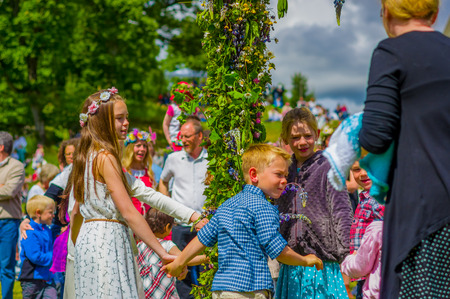 maypole: GOTHENBURG, SWEDEN - JUNE 19, 2015: Cheerful people dancing around the maypole during Midsummer celebration in Gunnebo Castle