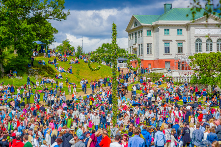 midsummer pole: GOTHENBURG, SWEDEN - JUNE 19, 2015: Cheerful people dancing around the maypole during Midsummer celebration in Gunnebo Castle