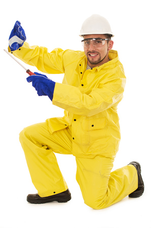 work gloves: man with screwdriver in yellow rain protective suit Stock Photo