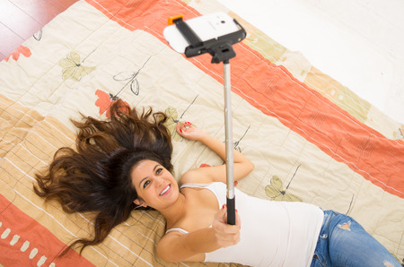 bedsheets: Pretty brunette wearing denim jeans and white top lying down on bedsheets hair spread out, holding selfie stick with mobile phone posing. Stock Photo