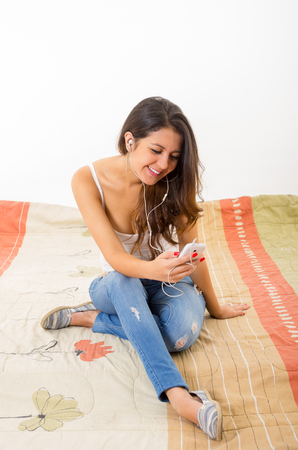 bedsheets: Pretty brunette wearing denim jeans and white top sitting down on brown red colored bedsheets, looking at phone screen smiling.