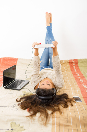 bedsheets: Pretty brunette wearing denim jeans white top lying down on bedsheets daydreaming with smartphone, laptop and tablet. Stock Photo