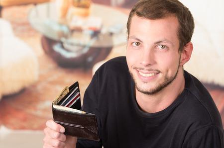 looking into camera: Hispanic male wearing dark sweater looking into camera holding up his wallet revealing its content.