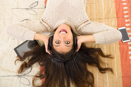 bedsheets: Pretty brunette wearing denim jeans white top lying down on bedsheets daydreaming with smartphone and tablet.