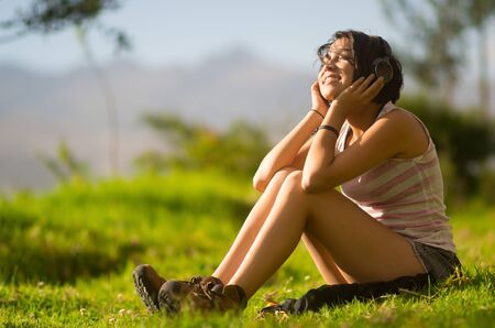 looking upwards: Pretty teenage hispanic girl sitting on grass, wearing headphones and looking upwards smiling. Stock Photo