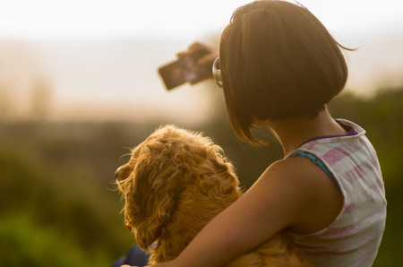 shot from behind: Teenage hispanic girl wearing striped top sitting with dog embracing and taking a selfie, shot from behind. Stock Photo
