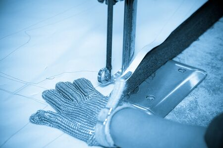 industrial machine: Hands wearing protection gloves using industrial machine for cutting carpets, textiles and other heavy duty fabrics. Stock Photo