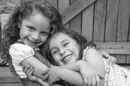 looking into camera: Adorable young brunette girls embracing hugging showing love and friendship, looking into camera black white edition. Stock Photo