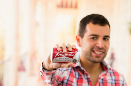 budweiser: QUITO, ECUADOR - AUGUST 3, 2015: Attractive young smiling man holding a Budweiser can