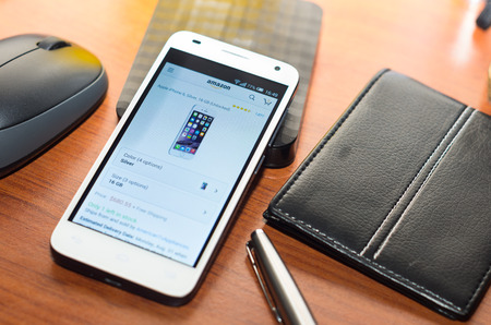 ebay: QUITO, ECUADOR - AUGUST 3, 2015: White smartphone lying on wooden desk with Ebay website screen next to a pen, wallet and mouse, business communication concept. Editorial
