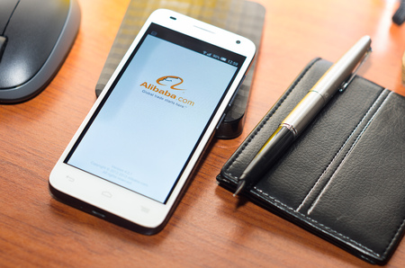alibaba: QUITO, ECUADOR - AUGUST 3, 2015: White smartphone lying on wooden desk with Alibaba website screen next to a pen, wallet and mouse, business communication concept.