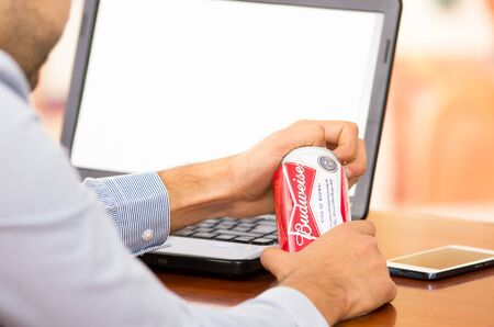 buisness: QUITO, ECUADOR - AUGUST 3, 2015: Young buisness man opening a Budweiser can in front of his laptop computer Editorial