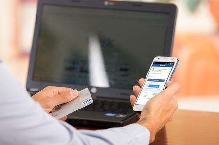 tarjeta visa: QUITO, ECUADOR - 03 de agosto 2015: El primer de mans jóvenes manos sosteniendo teléfono inteligente con Facebook visibles, tarjeta Visa en el otro lado con el ordenador portátil sentado en el escritorio. Editorial