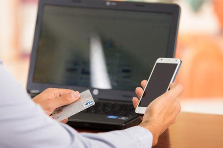 tarjeta visa: QUITO, ECUADOR - 03 de agosto 2015: El primer de mans jóvenes manos sosteniendo teléfono inteligente con una mano, tarjeta Visa en otra con el ordenador portátil sentado en el escritorio. Editorial