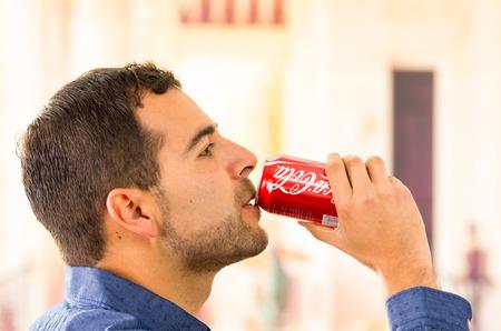 Quito, Ecuador - 3 augustus 2015: De aantrekkelijke jonge man het drinken van een Coca-Cola kan