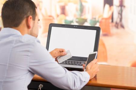 tarjeta visa: QUITO, ECUADOR - 03 de agosto 2015: El primer de mans jóvenes manos sosteniendo teléfono inteligente arriba, tarjeta Visa en el otro lado con el ordenador portátil sentado en el escritorio.