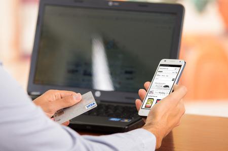tarjeta visa: QUITO, ECUADOR - 03 de agosto 2015: El primer de mans jóvenes manos sosteniendo teléfono inteligente con el sitio web Amazone visible, tarjeta Visa en el otro lado con el ordenador portátil sentado en el escritorio. Editorial