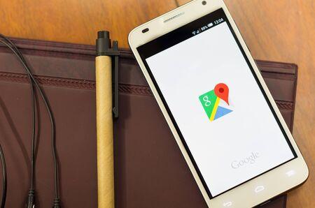 QUITO, ECUADOR - 3 augustus 2015: Witte smartphone liggend op bureau met Google maps scherm open naast een pen en een koptelefoon, zakelijke communicatie concept.