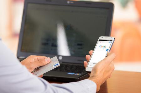 tarjeta visa: QUITO, ECUADOR - 03 de agosto 2015: El primer de mans jóvenes manos sosteniendo teléfono inteligente con sitio web de Google visible, tarjeta Visa en el otro lado con el ordenador portátil sentado en el escritorio.