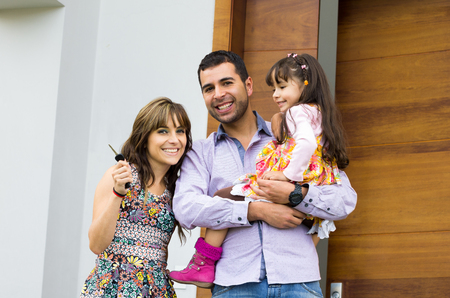 family in kitchen: Adorable hispanic family of three posing for camera outside front entrance door.