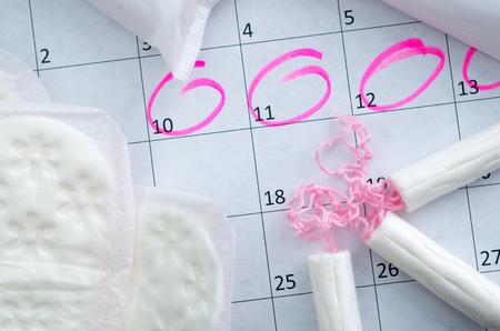 Calendrier blanc avec des cercles roses autour de la période de la date de menstruation et les tampons de nettoyage se trouvant sur le dessus.