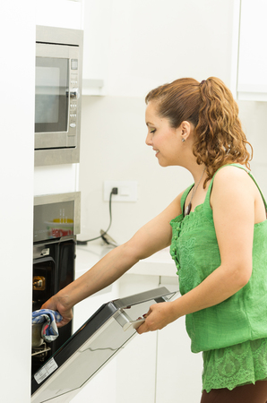 hispanic girl: Woman wearing green top in modern kitchen holding mittens and opening oven door. Stock Photo