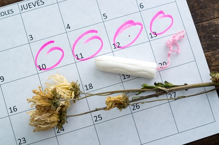 gynecologic: White calendar with pink circles around menstruation date period and clean tampons lying on top.