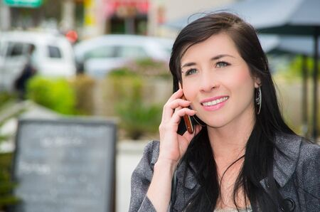 telephoning: Classy latina model wearing smart casual clothes walking in urban street talking on her mobile phone. Stock Photo