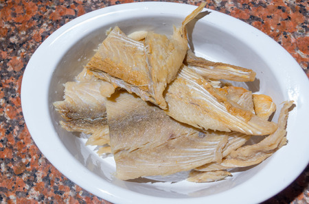 drained: Pieces of dry fish lying on white plate drained in water, preparation fanesca concept. Stock Photo