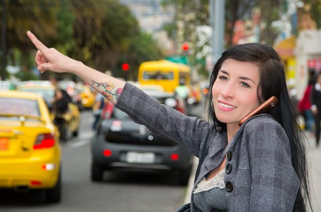 signalling: Classy latina model wearing smart casual clothes walking in urban street holding arm out signalling for taxi while talking on phone.