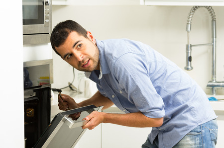looking towards camera: Hispanic male wearing blue shirt in modern kitchen leaning towards open oven door holding a fork looking past camera. Stock Photo
