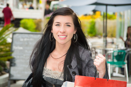 looking towards camera: Classy latina model wearing smart casual clothes sitting at streetcafe looking towards camera smiling.