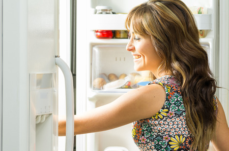 Woman wearing colorful dress in modern kitchen opening fridge door and reaching inside.