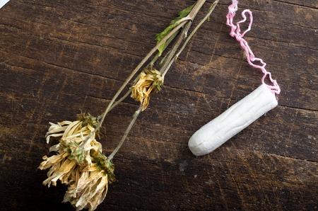 gynecologic: Clean white tampons lying on wooden surface with yellow colored dry flowers around.
