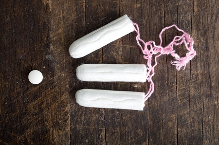 Clean white tampons lying on wooden surface. Stock Photo
