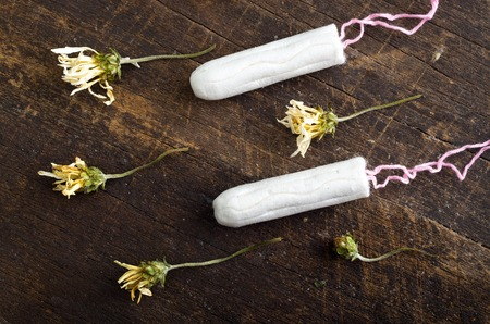 Clean white tampons lying on wooden surface with yellow colored dry flowers around.