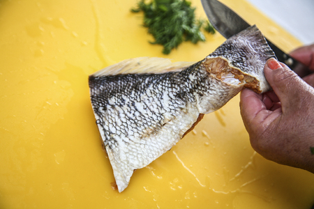 fish tail: Hands using knife to cut piece of fish tail on yellow surface, preparing fanesca concept.