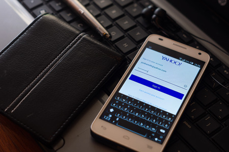 yahoo: QUITO, ECUADOR - AUGUST 3, 2015: White smartphone closeup lying next to silver pen and wallet on laptop keyboard with Yahoo website login screen visible.